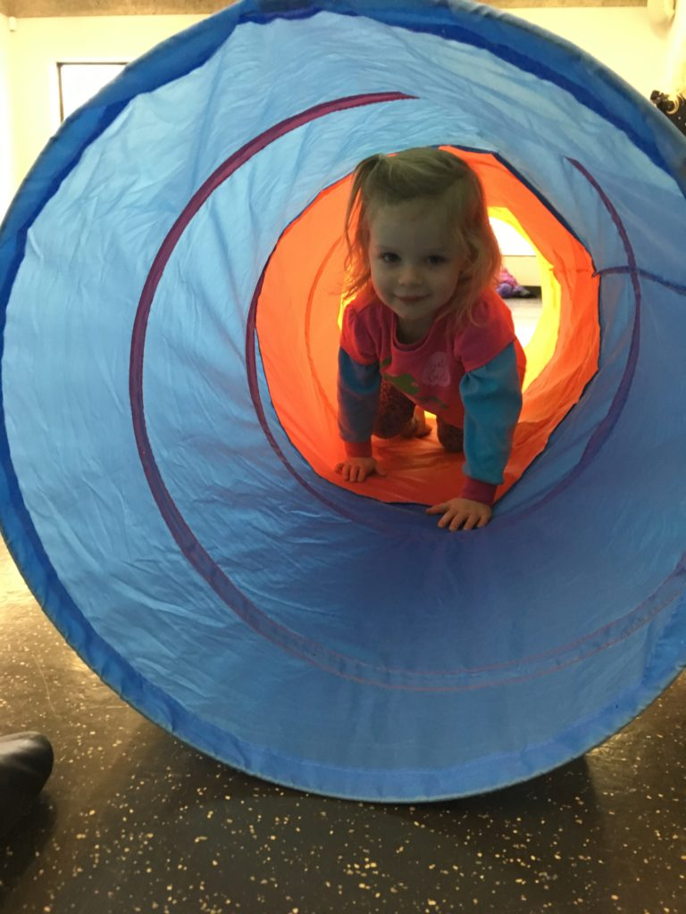 toddler crawling though a tube